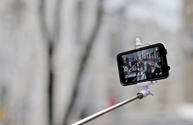 Família usa pau de selfie para tirar fotografia com smartphone, em Nova York (EUA). (Foto: Mary Altaffer/Associated Press)