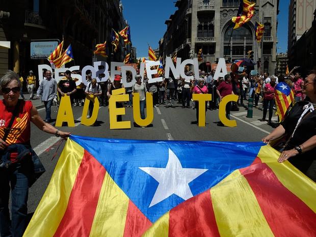 """Manifestantes levam cartazes com  """"Desobediência e adeus TC (Tribunal de Contas)"""" em Barcelona (Foto: Lluis Gene/ AFP)"""