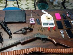 Uma espingarda calibre 12, um revólver calibre 32 e telefones celulares estiveram entre os materiais apreendidos (Foto: Ascom/Polícia Civil)
