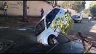 Carro fica com rodas suspensas após cair em buraco