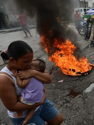 Mãe carrega o filho enquanto sai de área que será desocupada nas Filipinas (Foto: Ted Aljibe/AFP)