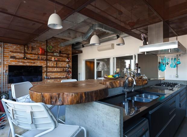 Integrada a cozinha tem bancada de concreto desenhada pelo arquiteto e executada pelo empreiteiro Edmilson Novaes. O tampo é de uma peça de madeira da Tora Brasil. Armários executados pela Marcenaria Zanatta (Foto: Divulgação)