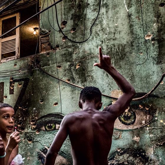 Garoto brinca em frente a parede crivada de balas na Rocinha (Foto:  Ana Carolina Fernandes/ÉPOCA)
