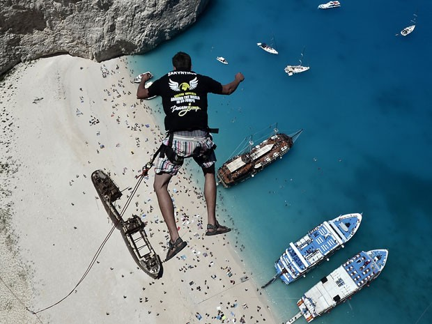 Membro do grupo salta sobre praia na Grécia (Foto: Louisa Gouliamaki/AFP)