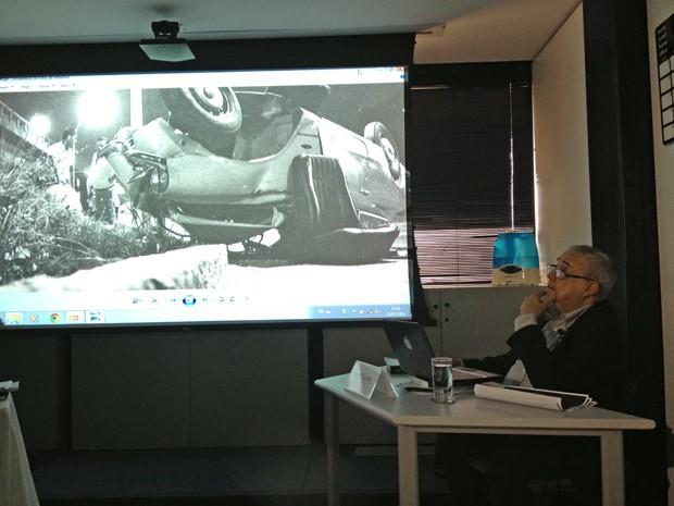 Cláudio Guerra observa foto de acidente que causou a morte da estilista Zuzu Angel (Foto: Felipe Néri / G1)