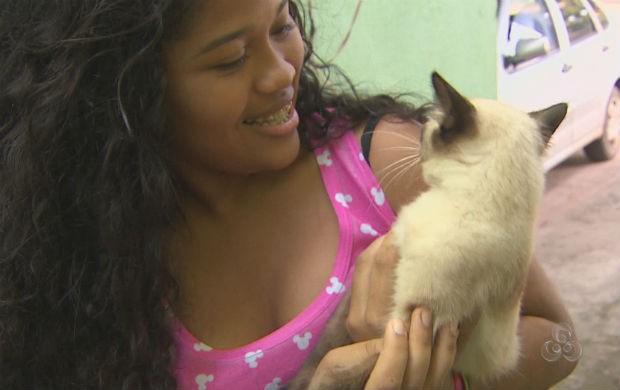 Adolescente cuidando do seu gato. (Foto: Reprodução/TV Amapá)