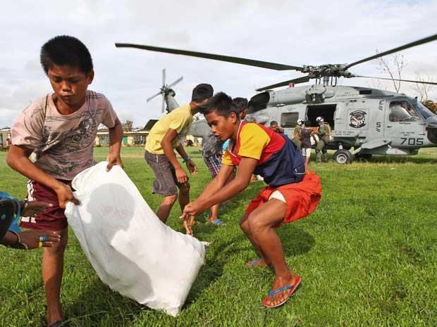 Jovens ajudam a descarregar mercadorias de helicóptero em região atingida pela tormenta. (Foto: Dita Alangkara / AP Photo)