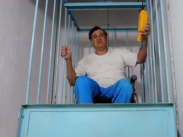 Hernesto usa elevador para ajudar na pintura (Foto: Luiz Ferreira/G1)