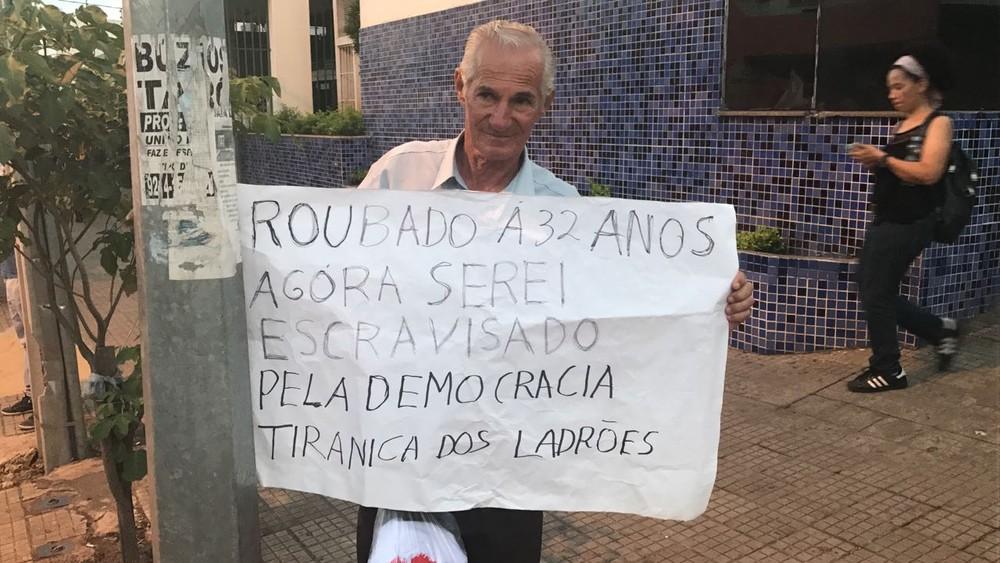 Adelfonso Muniz, de 71 anos, carregou cartaz durante ato (Foto: Lislaine dos Anjos/ G1)