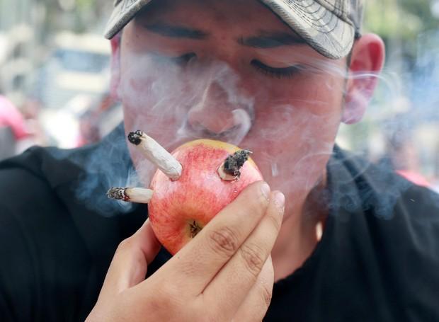 Homem fuma maconha com cachimbo improvisado (Foto: Fredy Builes/Reuters)