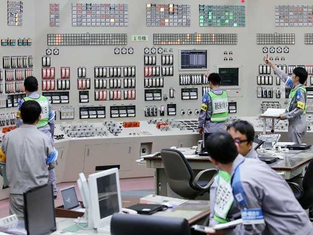 Operadores reiniciam o reator nuclear na sala de controle central da usina de Sendai (Foto: Jiji Press / via AFP Photo)