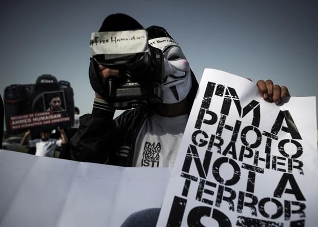 Manifestante carrega máquina e cartaz em apoio ao fotógrafo preso (Foto: Mohammed Al-Shaikh/AFP)
