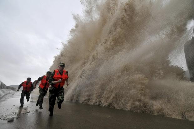 Guardas de fronteira fogem de onda gigante na costa durante a aproximação do tufão Fitow, em Wenling, na província de Zhejiang, neste domingo (6) (Foto: Reuters)