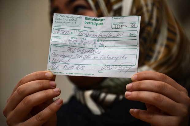 Mulher síria está refugiada na estação de trem em Milão (Foto: GIUSEPPE CACACE/ AFP)