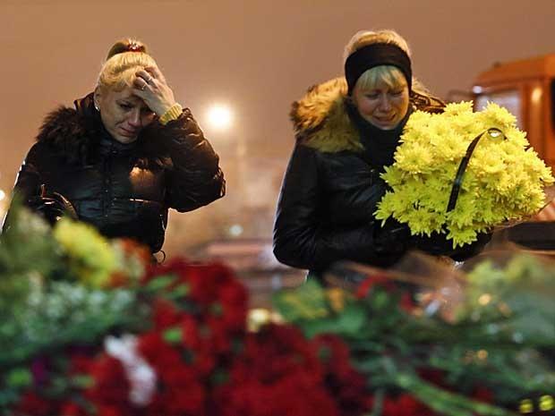 Mulheres deixam flores na estação ferroviária de Volgogrado, na Rússia. (Foto: Denis Tyrin / AP Photo)