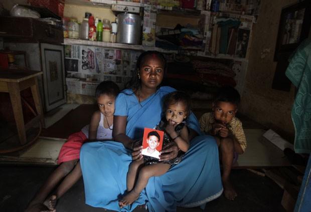 Com seus outros filhos, Pinky Devi, que vive em Nova Délhi, mostra foto de seu outro filho, Ravi Shankar, que desapareceu há três anos  (Foto: Manish Swarup/AP)