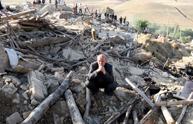 Homem fica no meio de destroços de casa destruída na vila de Baje-Baj, no Irã (Foto: AFP)