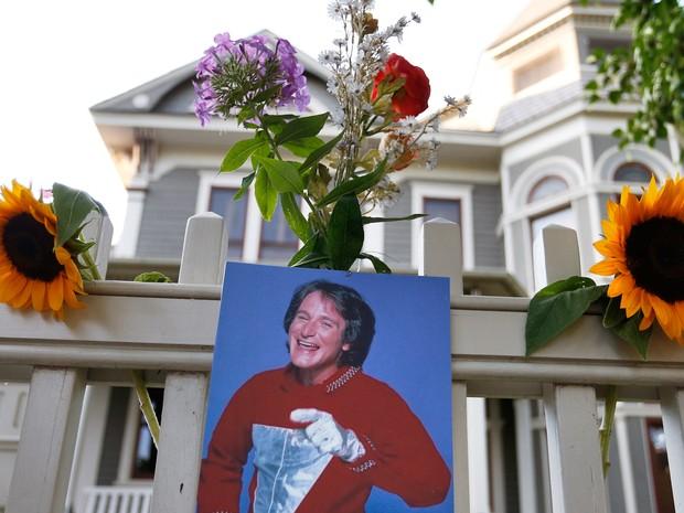 """Com flores e uma foto de Robin Williams como Mork da série de TV """"Mork & Mindy"""", que fez muito sucesso na década de 1980, fãs prestam homenagem ao ator em uma casa no Colorado. O local teve sets de gravação da série (Foto: Brennan Linsley/AP Photo)"""