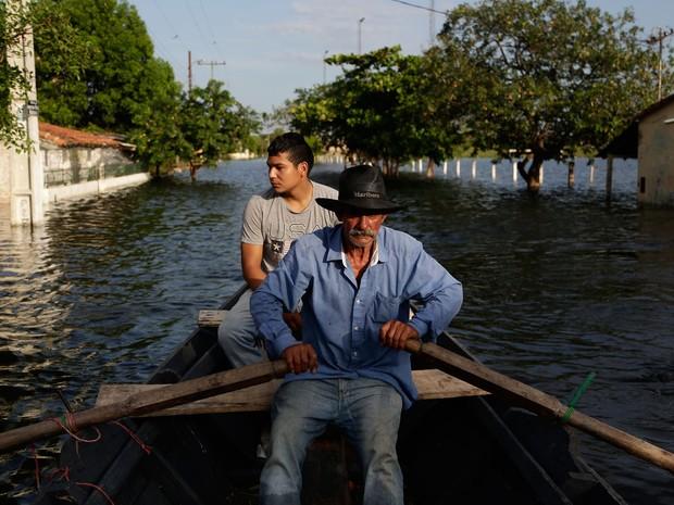 Víctor Ferreira, que deixou sua casa por causa da inundação, rema pelas ruas do bairro Jukyty, em Assunção, no Paraguai, na quarta (23) (Foto: Foto AP/Jorge Sáenz)
