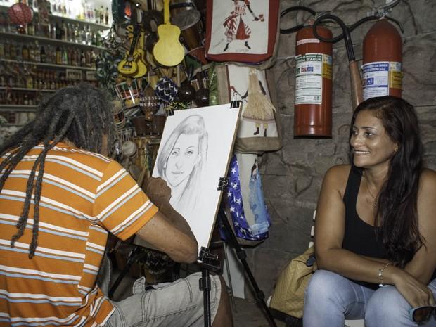 Artista plástico desenha rosto de visitante do Mercado Modelo (Foto: Egi Santana/G1)