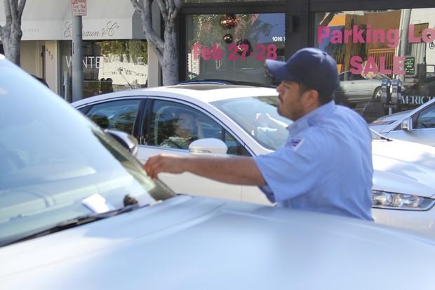 Agente de trânsito coloca bilhete no carro de Kanye West (Foto: AKM-GSI)