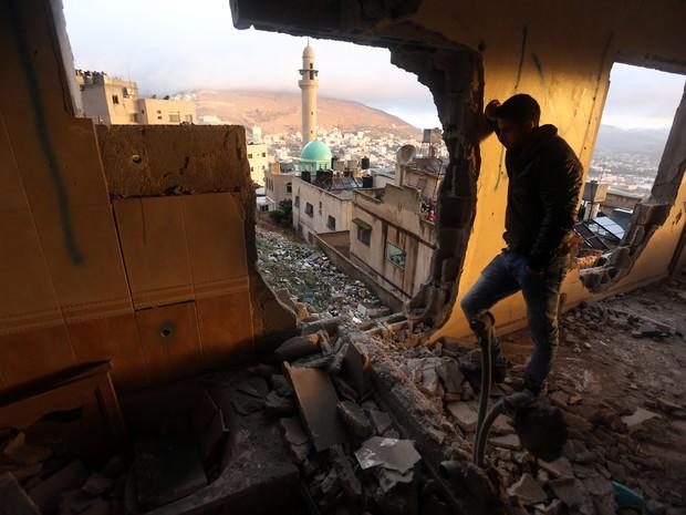 Palestino é visto em destroços da casa de Ragheb Ahmad Mohammad Alawi, acusado de matar um judeu israelense no dia 1º de outubro. O Exército de Israel destruiu sua casa nesta quinta-feira (3) (Foto: Jaafar Ashtiyeh/AFP)