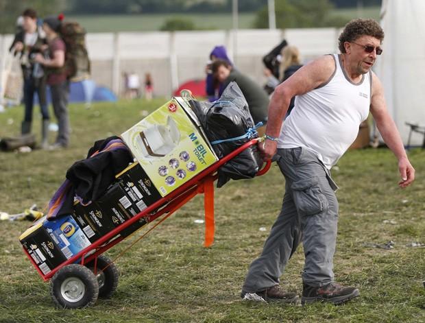 Homem usou carrinho para transportar caixas de cerveja e um banheiro portátil, para evitar qualquer tipo de aperto (Foto: Olivia Harris/Reuters)