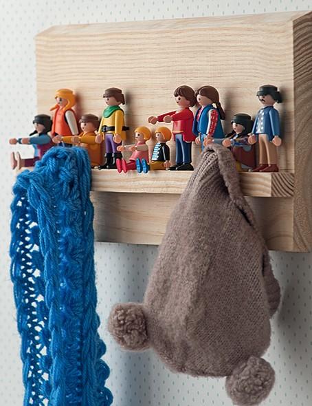 Os bonecos de Playmobil foram resgatados entre os brinquedos e fixados com cola quente a uma tábua de madeira. Ora sentados, ora em pé, eles acomodam roupas e chapéus