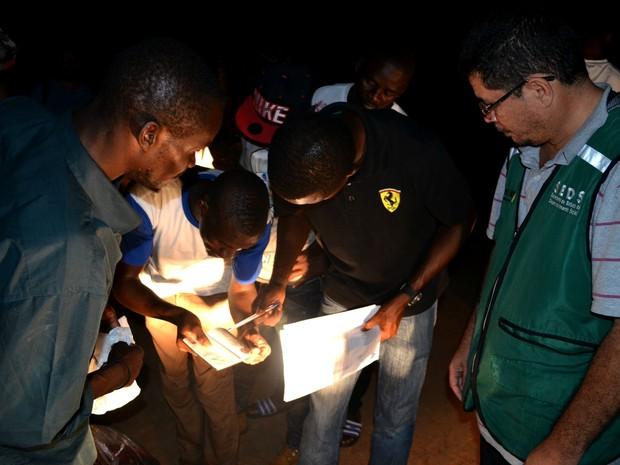 Equipe da Secretaria de Desenvolvimento Social do Acre (SEDS) confere lista de embarque dos imigrantes (Foto: Yuri Marcel/G1)