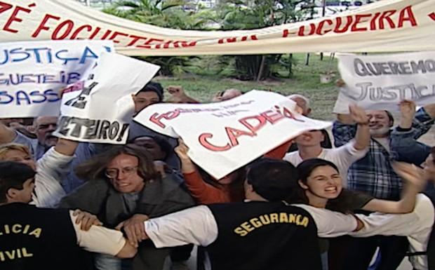 Uma multidão revoltada cerca a delegacia onde está Clementino