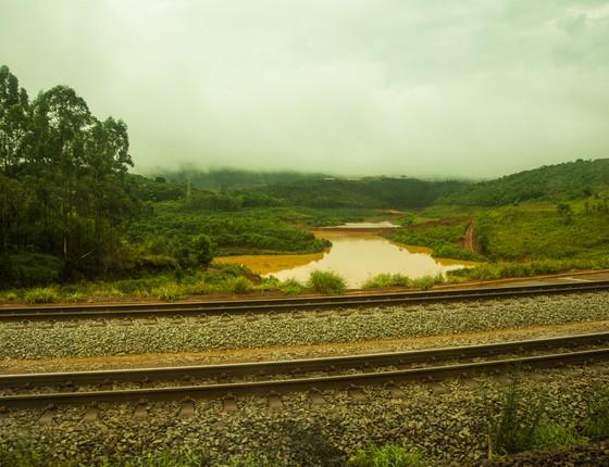 Rio Doce sujo de lama ao lado dos trilhos do trem (Foto: Camila Pastorelli)