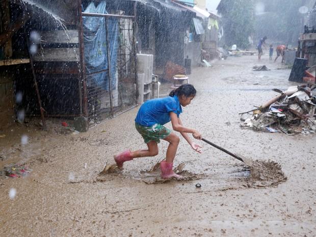 Garota filipina remove lama trazida pela chuva em San Mateo (Foto: REUTERS/Erik de Castro)
