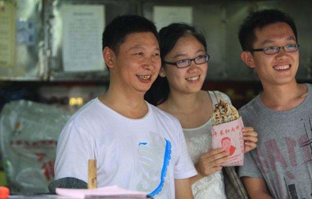 Turistas posam ao lado de Shao Jianhua, sósia do presidente chinês (Foto: AFP)