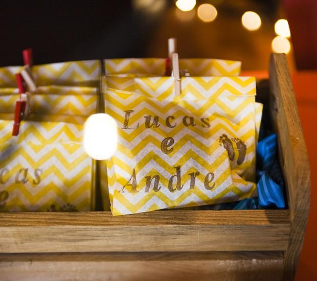 Além de fazer parte da decoração, você pode colocar docinhos dentro dos saquinhos estampados e dar de lembrancinha para os convidados.  A graça ficou por conta do carimbo com os nomes dos bebês e dos minipregadores coloridos.  (Foto: Divulgação)