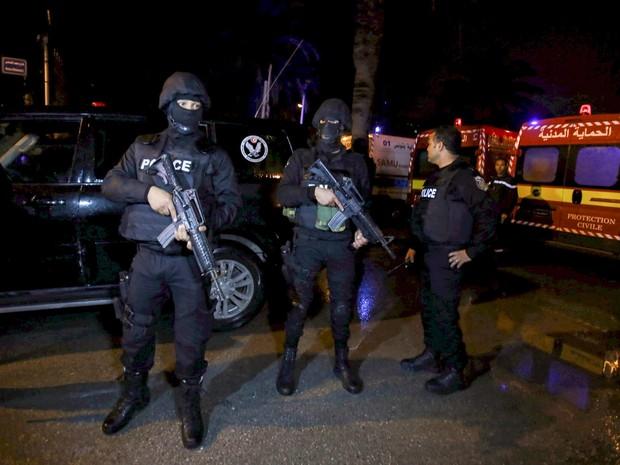 Policiais são vistos ao lado de uma ambulância após ataque em um ônibus militar em Tunis, na Tunísia. Pelo menos 11 pessoas morreram depois de uma explosão no ônibus que transportava guardas presidenciais em uma rua no centro da cidade (Foto: Zoubeir Souissi/Reuters)