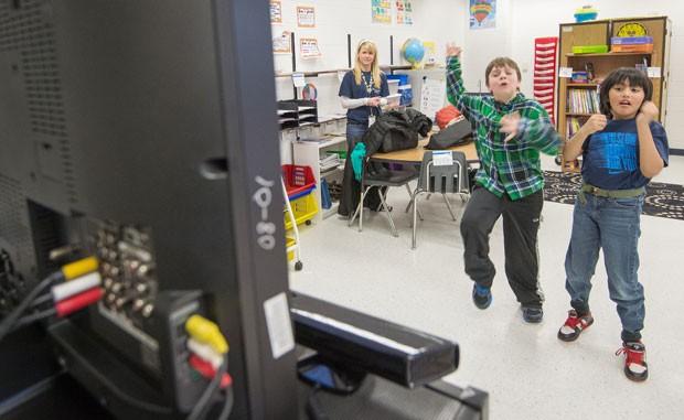 Sawyer Whitely (à esq.) e Michael Mendoza usam Xbox com Kinect em programa para autistas nos Estados Unidos (Foto: Paul J. Richards/AFP)