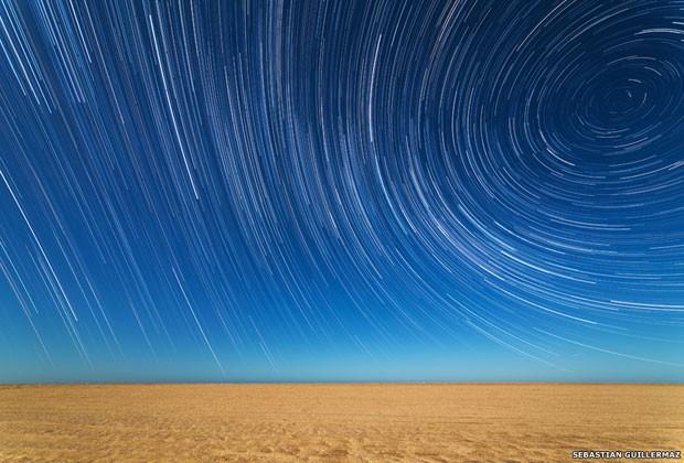 O argentino Sebastián Guillermaz também produziu esta fotografia das luzes das estrelas sob a praia em Mar de Ajo, em Buenos Aires. O fotógrafo utilizou várias imagens para criar um efeito de passagem do tempo (Foto: Sebastián Gutierrez/BBC)