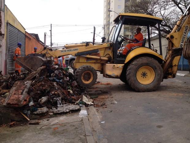 Escavadeira derruba paredes para perícia realizar buscas em imóvel ao lado da casa de pintor (Foto: Will Soares/ G1)