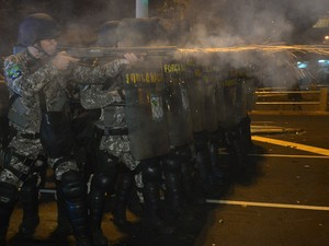 Policiais atiram contra grupo de manifestantes (Foto: Yasuyoshi Chiba/AFP)