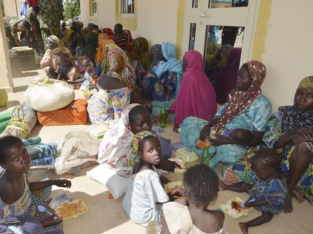 Mulheres e crianças resgatados do Boko Haram por soldados nigerianos recebem alimentos ao chegarem a posto militar em Maiduguri, na quinta (30) (Foto: AP Photo/Jossy Ola)