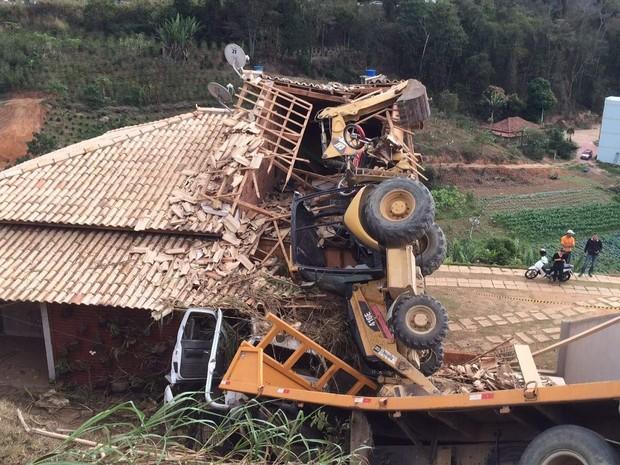 Caminhão que transportava um trator caiu sobre um casa em Venda Nova (Foto: VC no ESTV)
