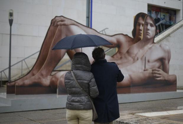 Casal observa o retrato gigante montado na estrutura de uma escada. A princípio, essa peça não passará por censura, segundo Klaus Pokorny (Foto: Alexander Klein/AFP)
