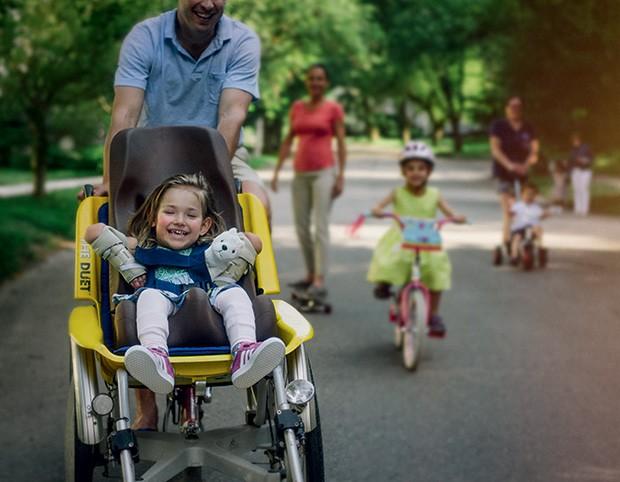 O sorriso genuíno de uma garota passeando em um carrinho adaptado. (Foto: Kate T. Parker)