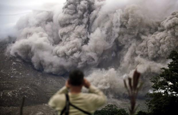 Homem observa erupção do Sinabung, em Tiga Serangkai (Foto: Binsar Bakkara/AP)