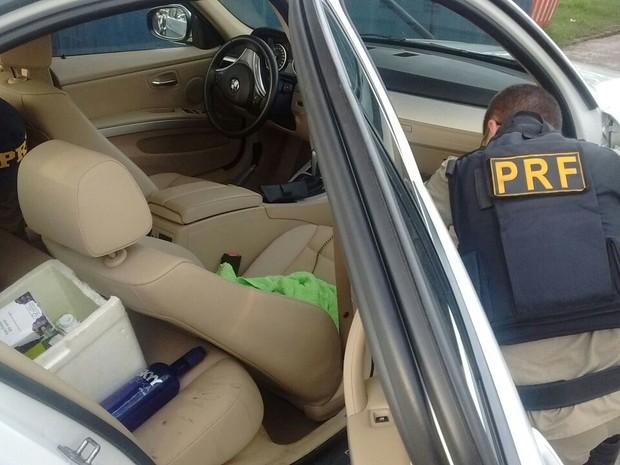 Garrafas de bebida alcóolica e arma de fogo foram encontrados pela PRF no veículo apreendido.  (Foto: Divulgação/ PRF)