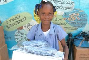 Criança haitiana recebe material escolar de verba doada para reconstrução do país (Foto: HRF/Divulgação)