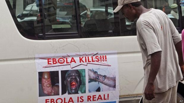 Homem observa cartaz advertindo sobre o ebola na Libéria, onde muitas pessoas duvidam que epidemia exista (Foto: AP)