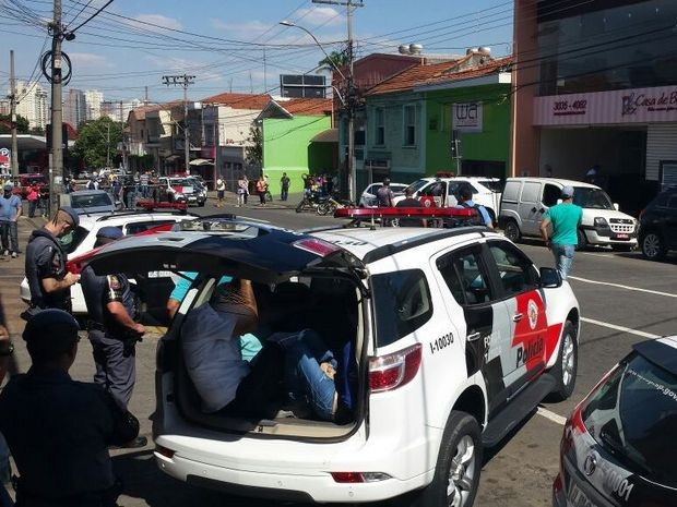 Suspeitos são colocados em carro da PM após tentativa de assalto a banco em Piracicaba (Foto: Claudia Assencio/G1)