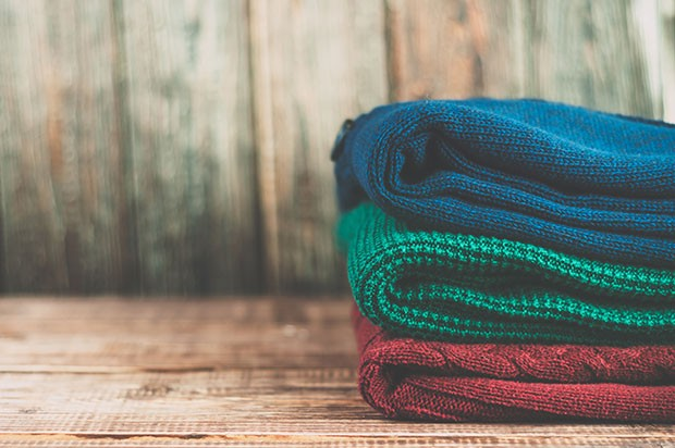 Warm clothes laid in a pile on wooden background.Colorful sweaters on a wooden table. (Foto: Getty Images/iStockphoto)