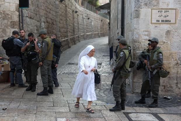 Freira passa por policiais em rua na Cidade Velha de Jerusalém neste domingo (4). Palestinos foram banidos da região por 48 horas (Foto: Menahem Kahana/AFP)